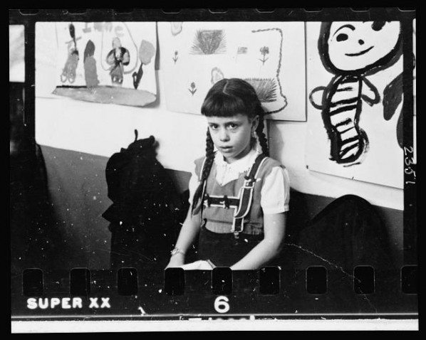 Young-girl-half-length-portrait-standing-against-wall-displaying-art-work-in-classroom-in-Chicago-Illinois-598x478